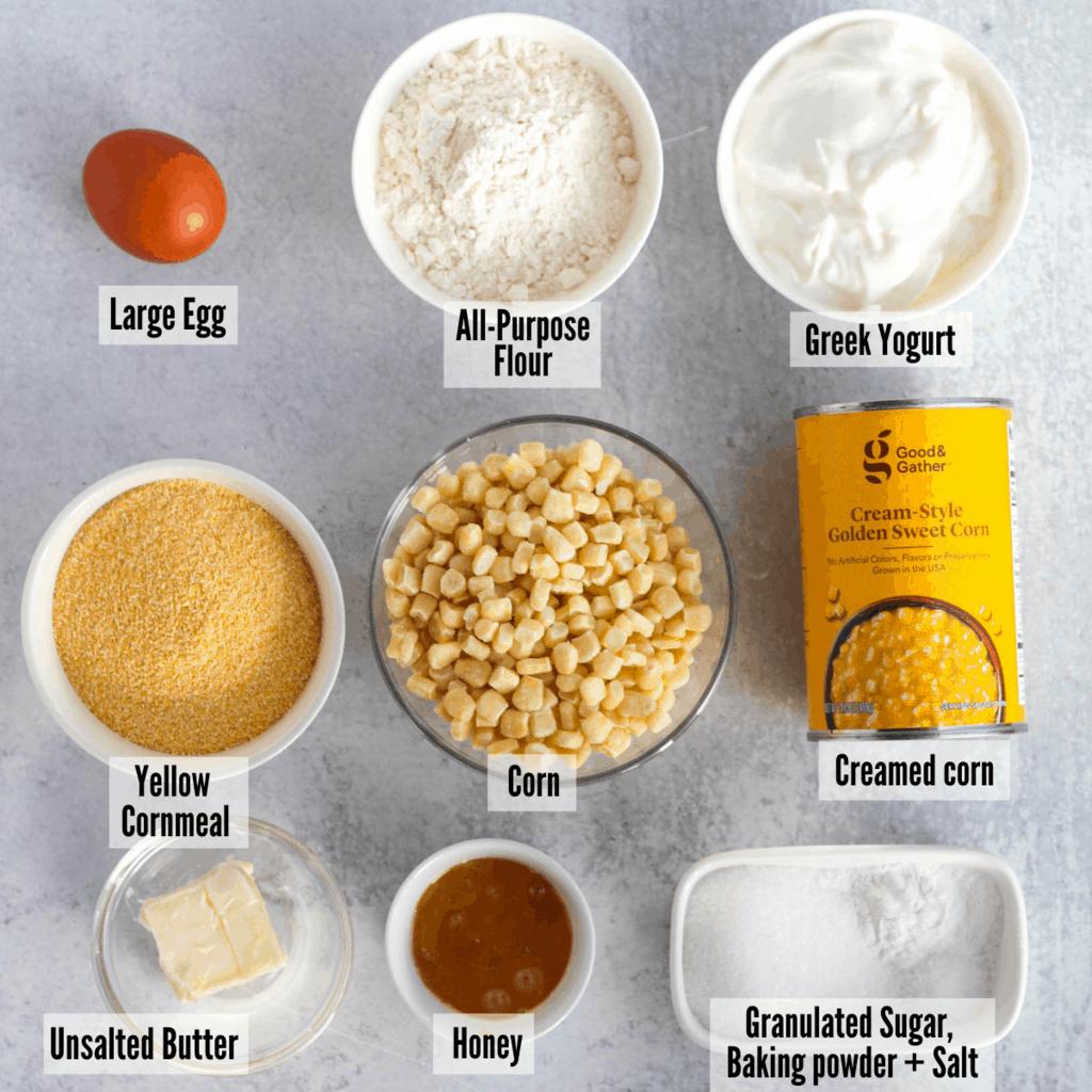 All the ingredients for corn souffle: large egg, all-purpose flour, Greek yogurt, creamed corn,  corn, yellow cornmeal, unsalted butter, honey, granulated sugar, baking powder, and salt