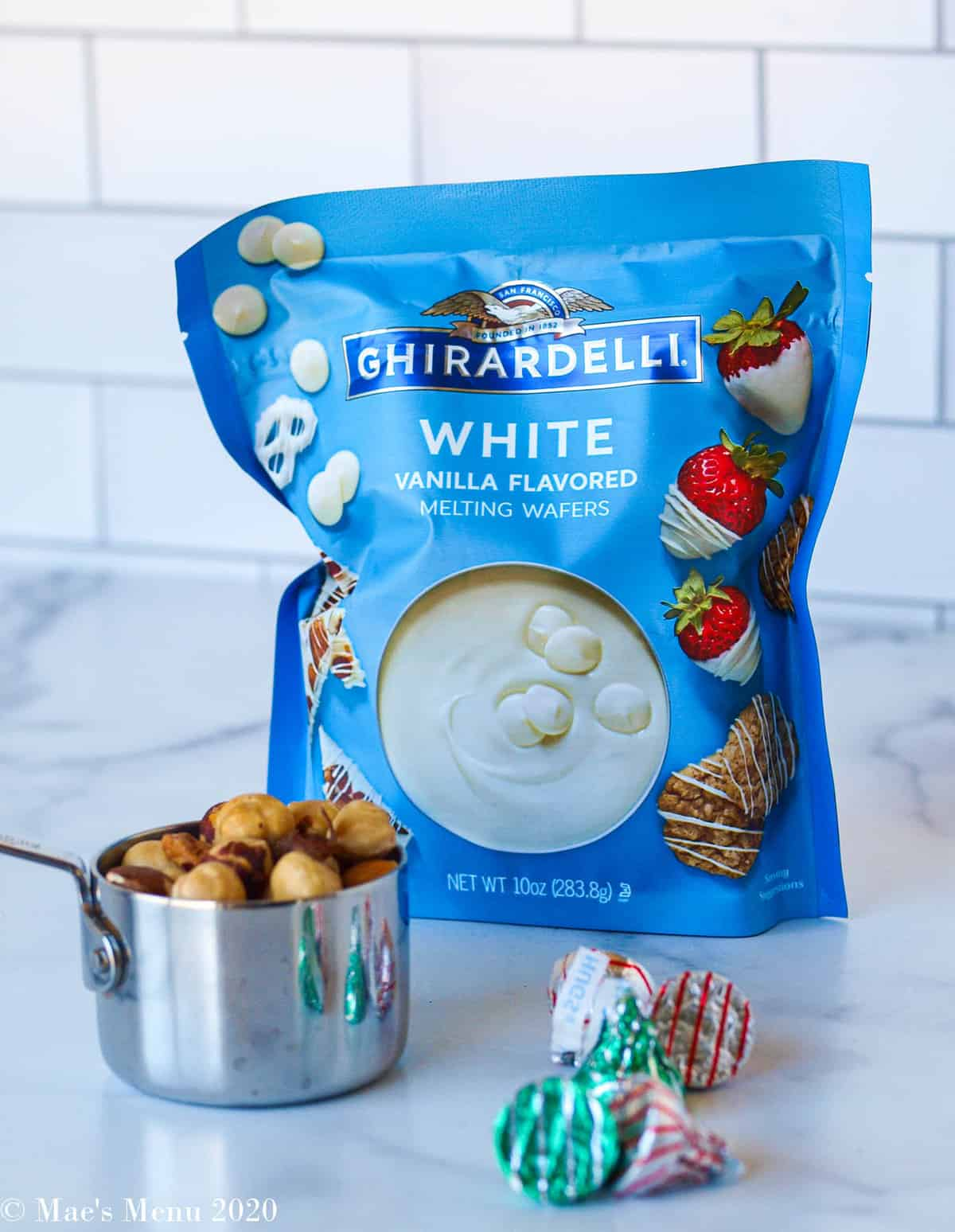 A bag of ghiradelli white chocolate discs, dry roasted hazelnuts, and hershey's hugs sitting on a counter