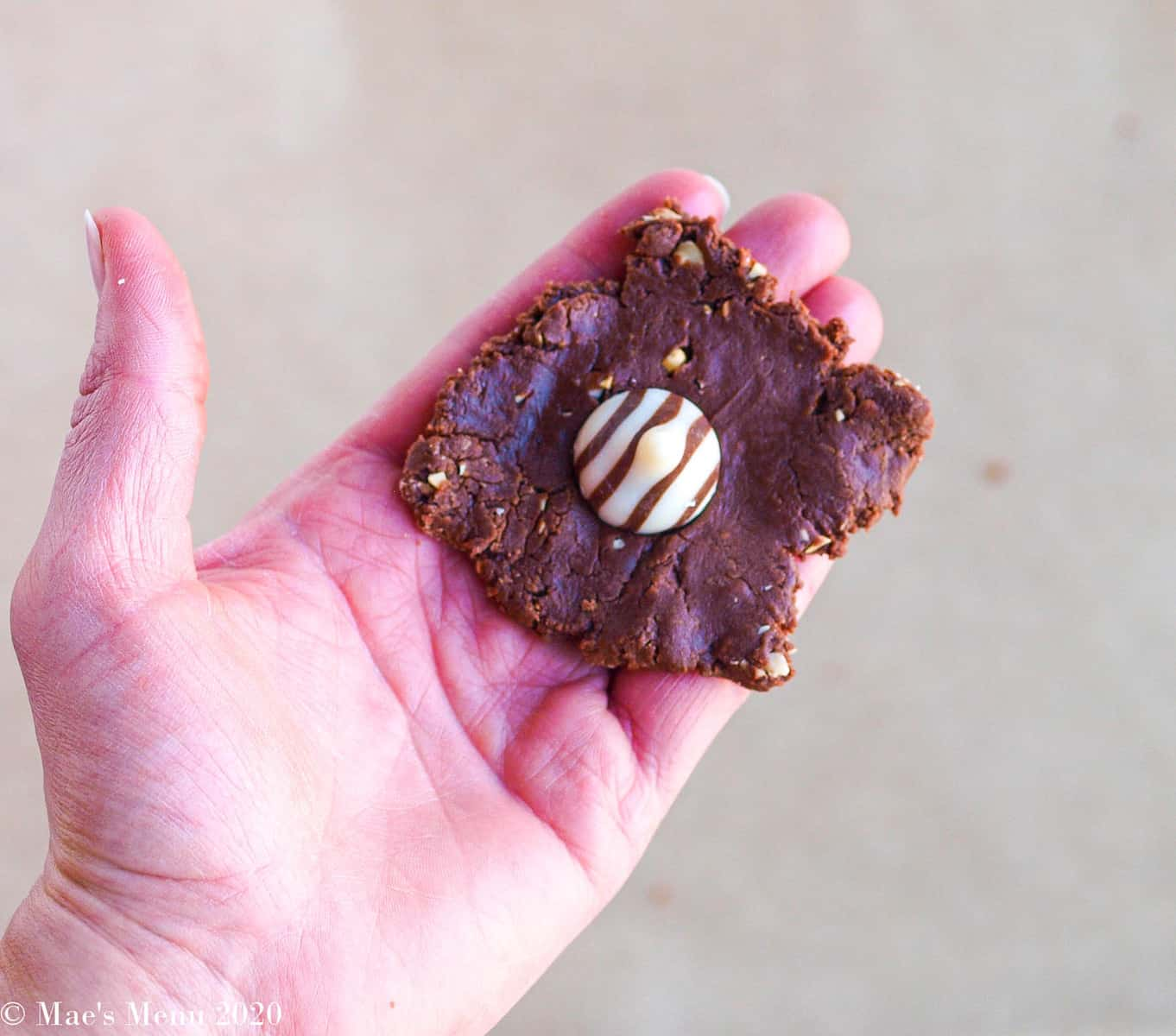A hand holding a disc of cookie dough with a Hershey's hug on top of it