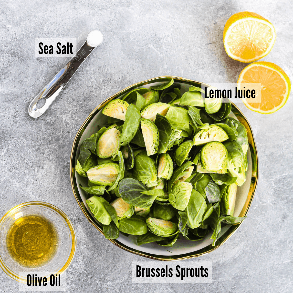 All the ingredients for air fryer brussel sprouts: salt, olive oil, lemon juice, and brussel sprouts