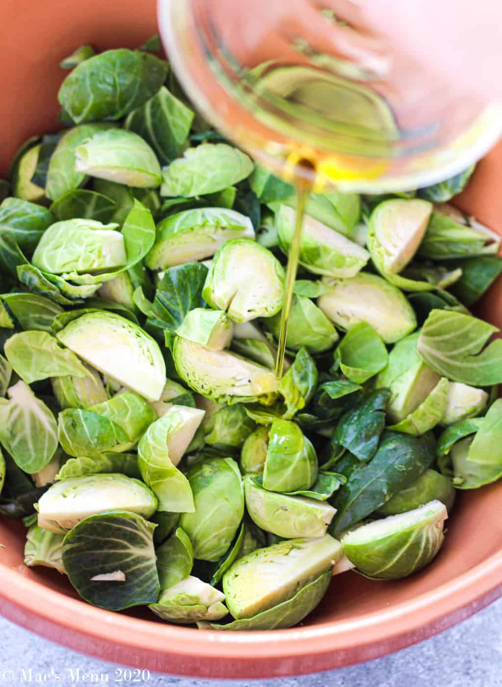 Pouring oil into a large bowl of brussels sprouts