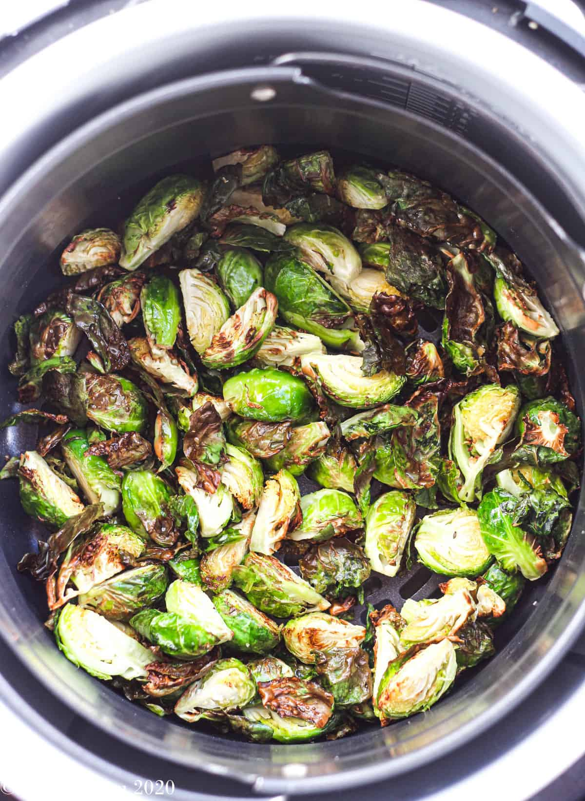 The brussels sprouts in the air fryer halfway through cooking