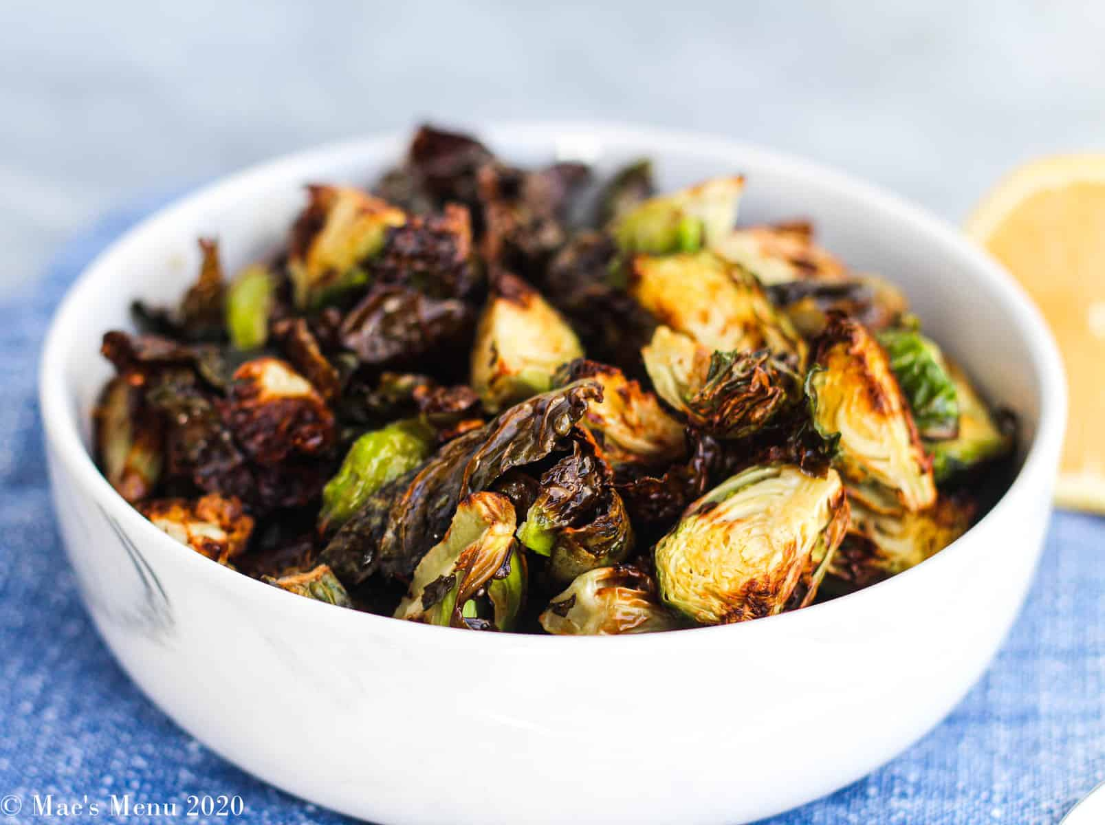 A side angle shot of a white bowl of air fryer brussels sprouts next to a lemon half