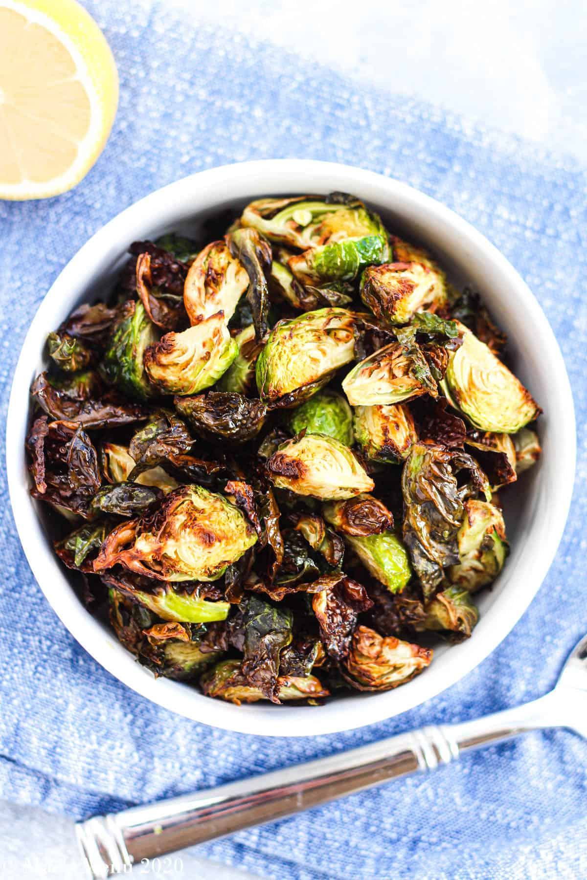 An overhead shot of a white bowl of air fryer brussel sprouts sitting on a blue towel