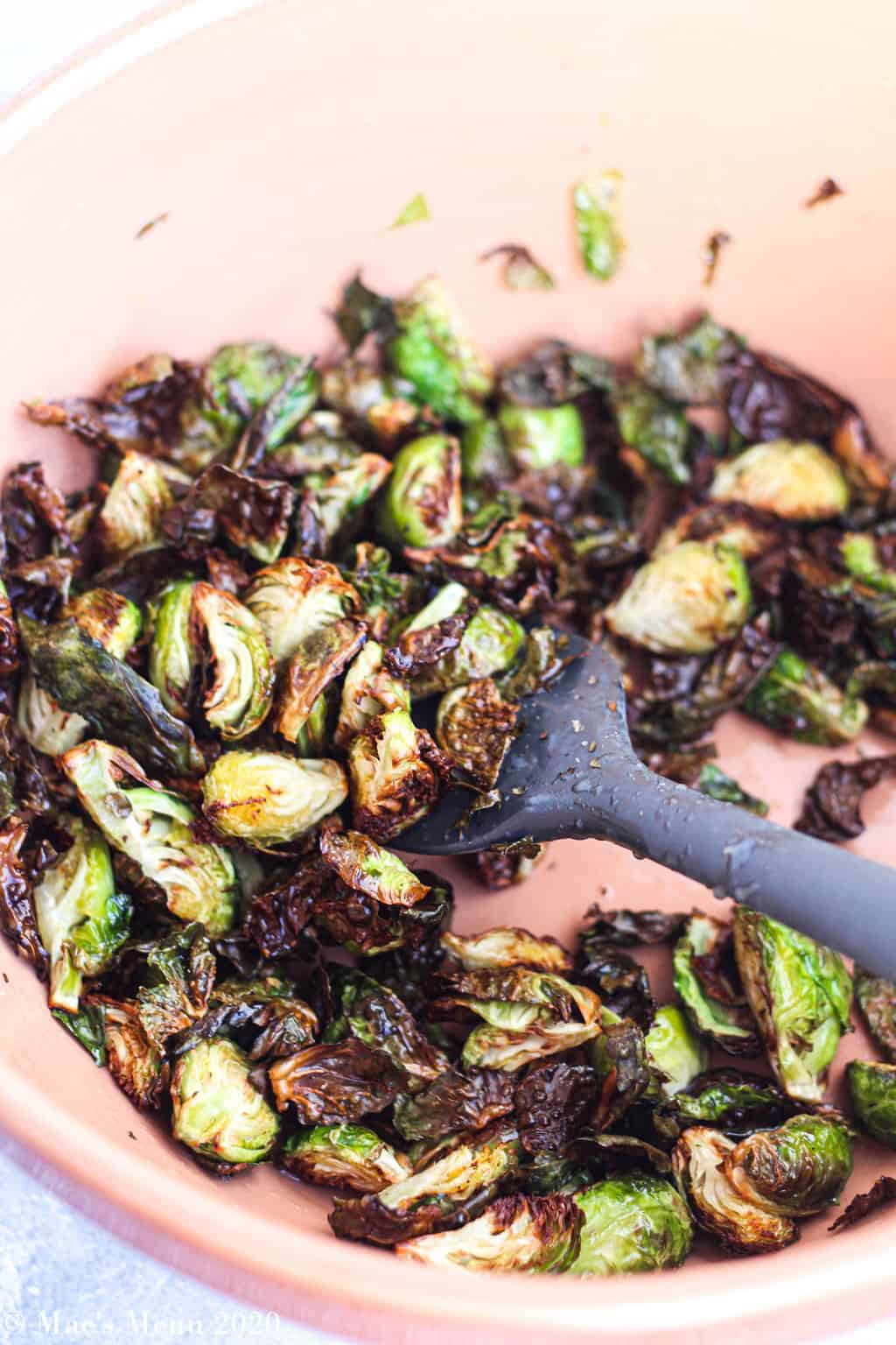 A large mixing bowl of air fryer brussel sprouts with a silicone spatula in it