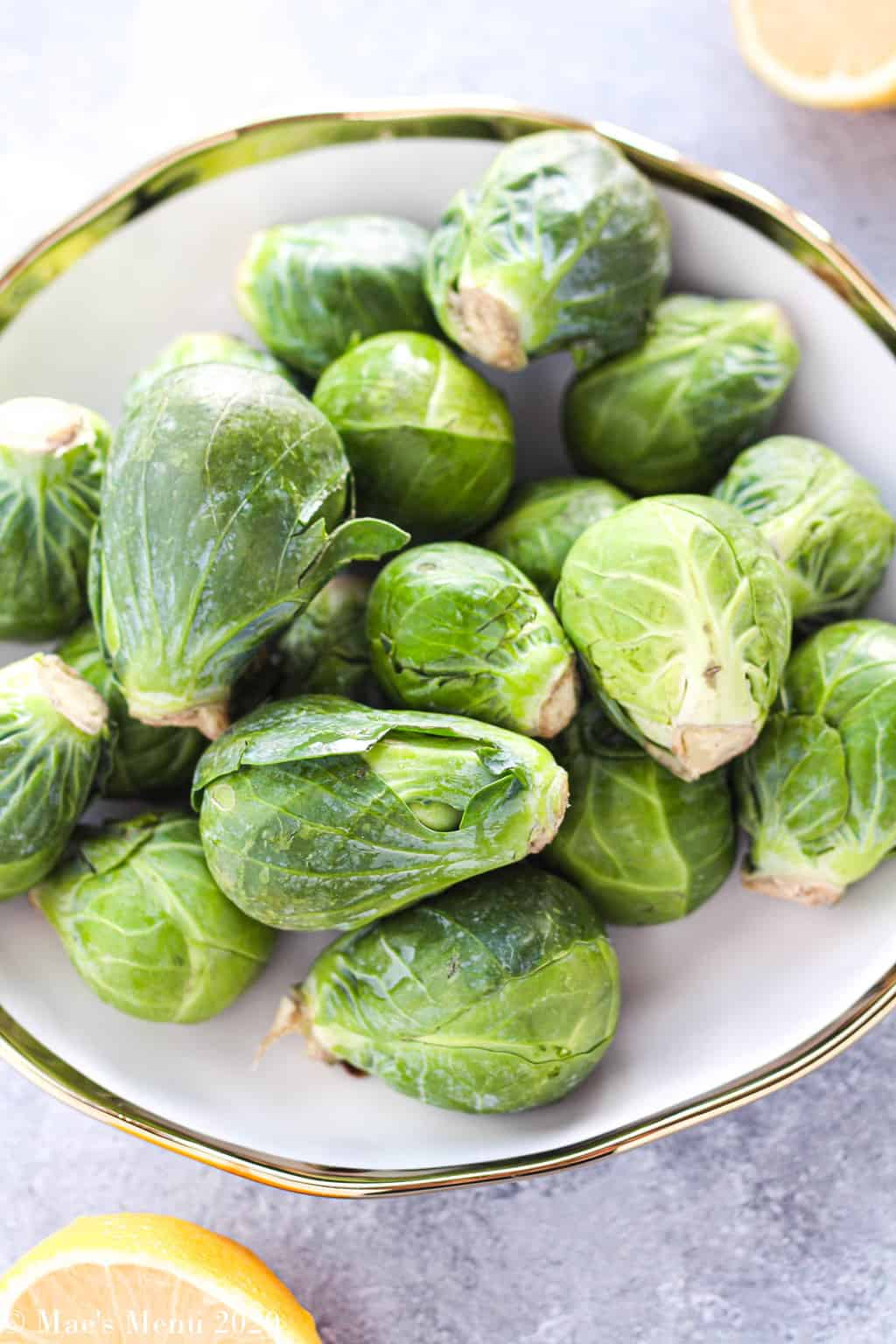 An up-close shot of a bowl of brussels sprouts with a lemon in the background