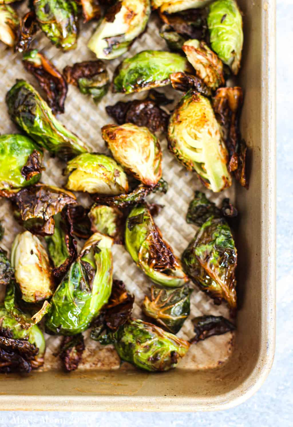 An upclose overhead shot of air fryer brussel sprouts on a baking pan