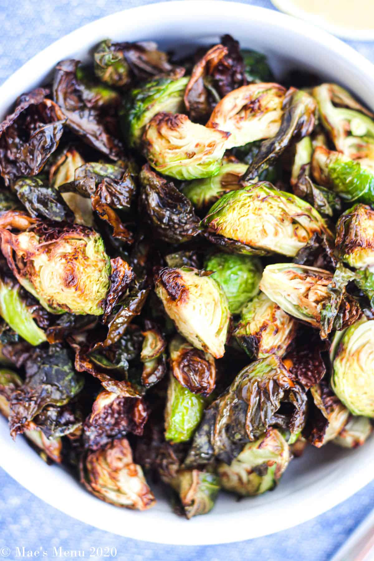 An up-close overhead shot of a bowl of air fryer brussels sprouts