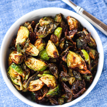 An overhead shot of a white bowl of air fryer brussels sprouts on a blue napkin