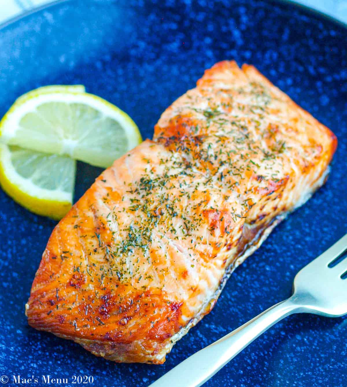 A piece of air fryer salmon on a dark blue plate next to slices of lemon