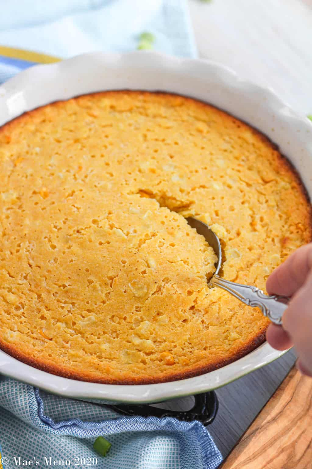Taking a scoop out of the dish of corn souffle