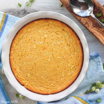 An overhead shot of a corn souffle in a deep dish pie pan