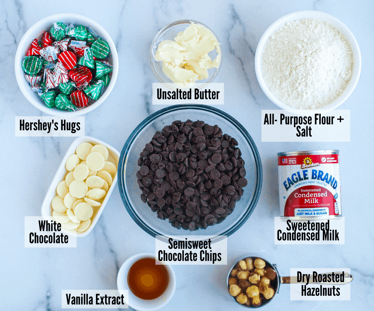 All the ingredients for these chocolate hazelnut fudgy bonbons: Hershey's hugs, unsalted butter, all purpose flour, salt, sweetened condensed milk, semisweet chocolate chips, white chocolate, vanilla extract, and dry roasted hazelnuts