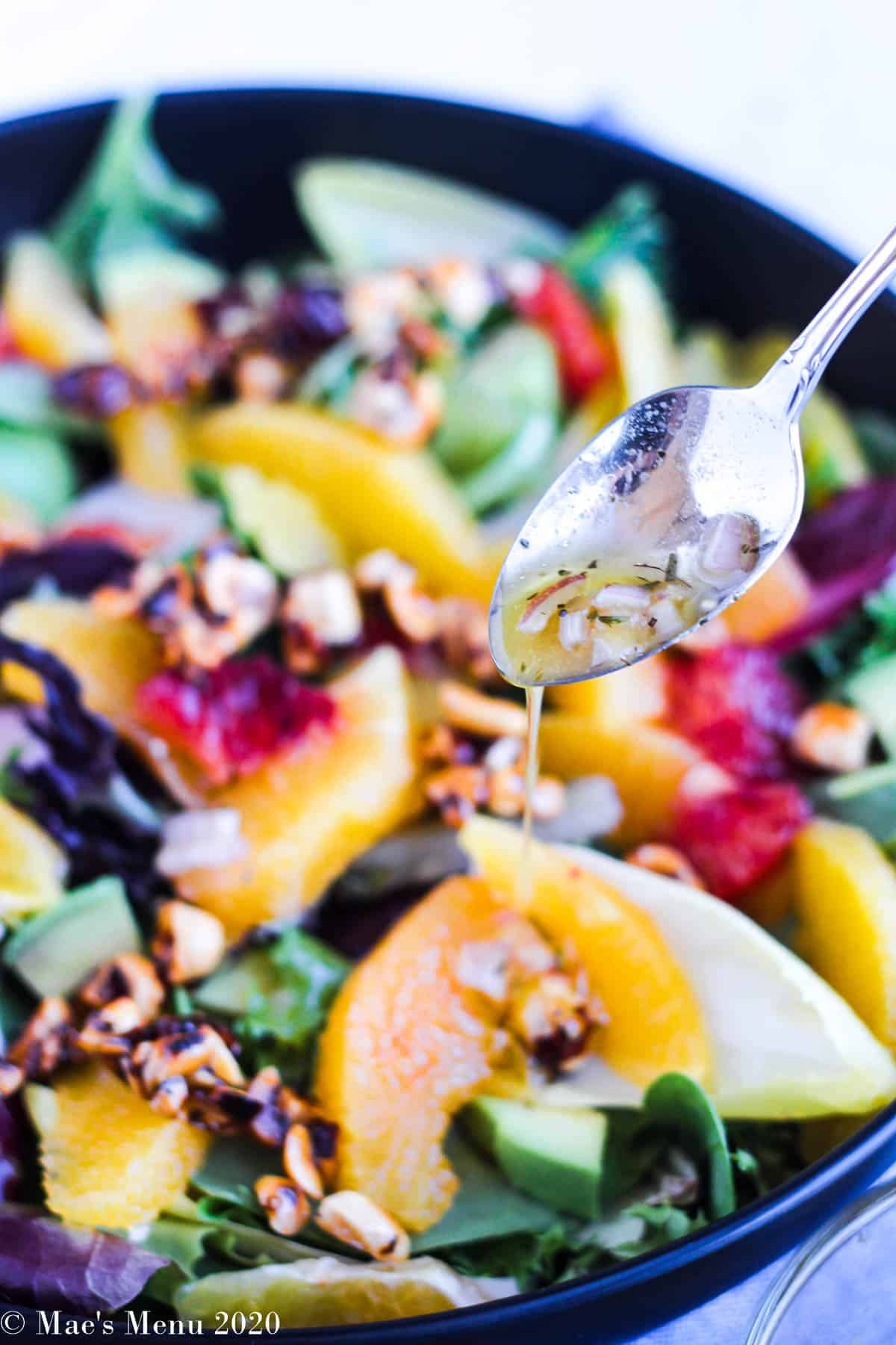 A small spoon drizzling dressing over the orange salad