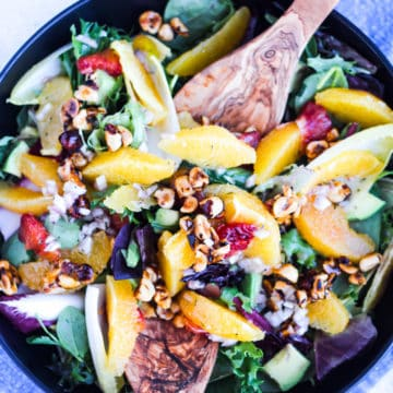 An overhead shot of a black bowl full of orange salad with honeyed hazelnuts with salad tongs in the salad