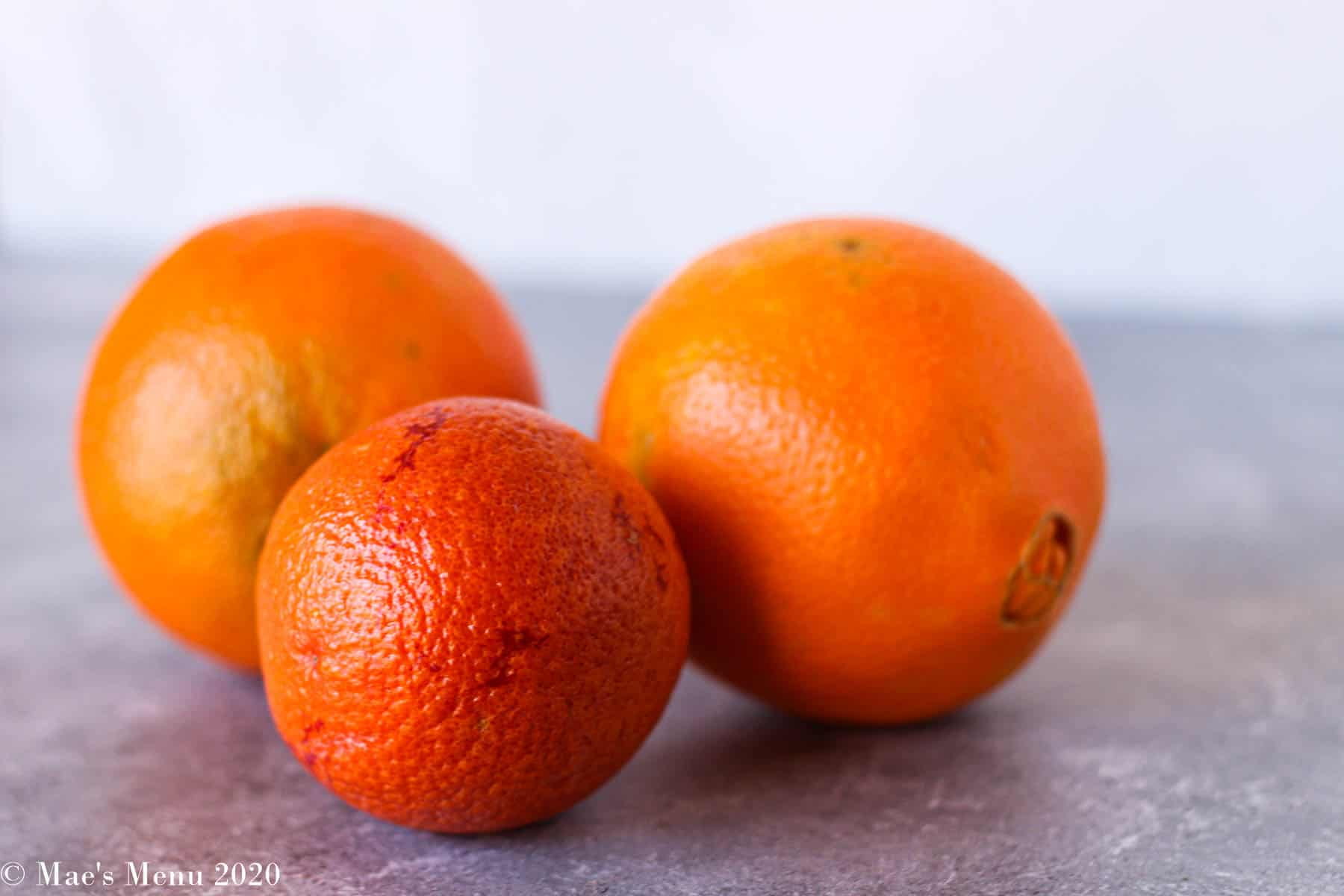 3 oranges sitting on a concrete counter