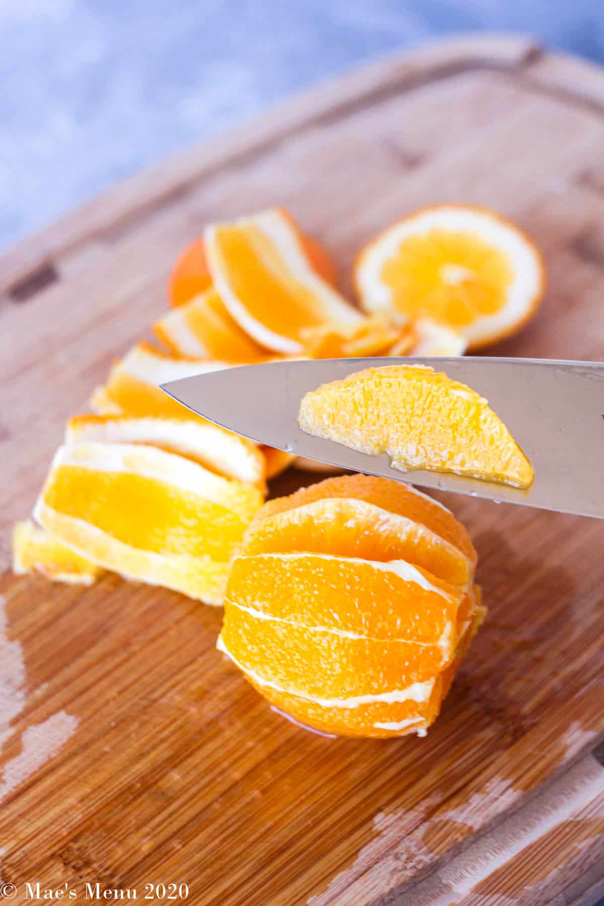 A knife pulling one of the orange segments out of the fruit