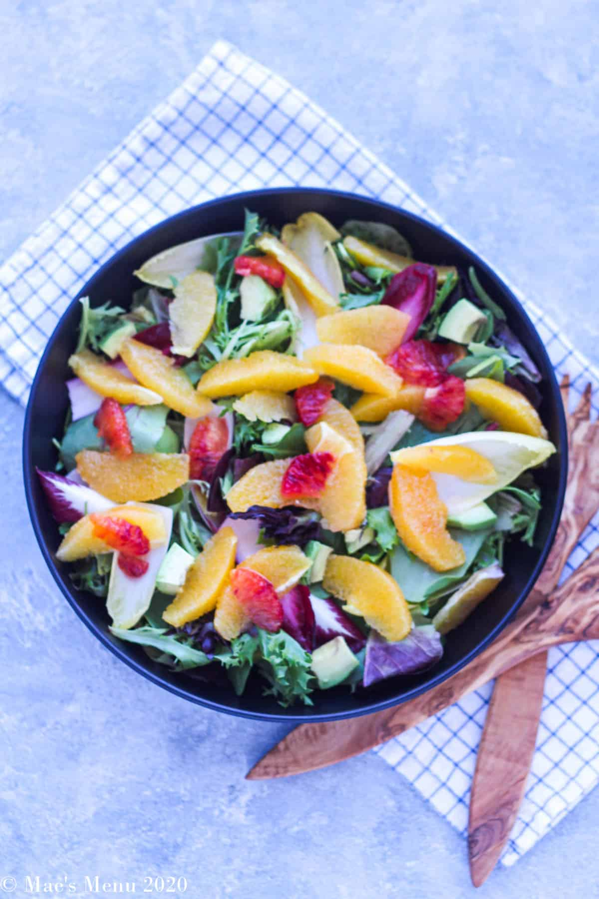 A compiled but undressed salad  in a black bowl
