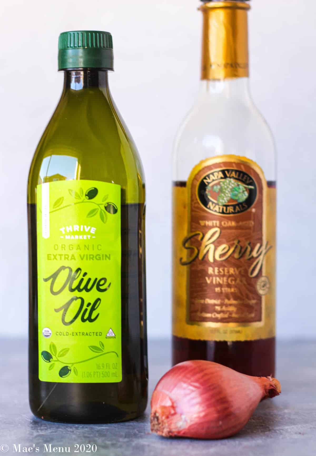 A bottle of thrive market olive oil, sherry vinegar, and a large shallot
