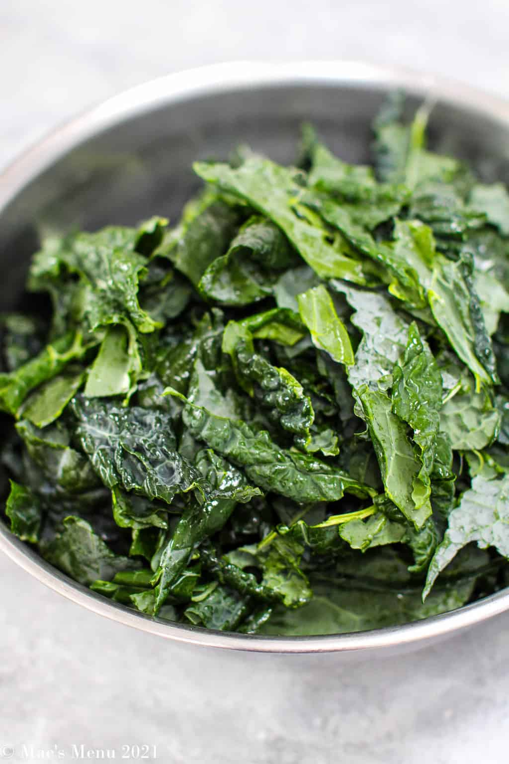 Pieces of kale in a large metal bowl