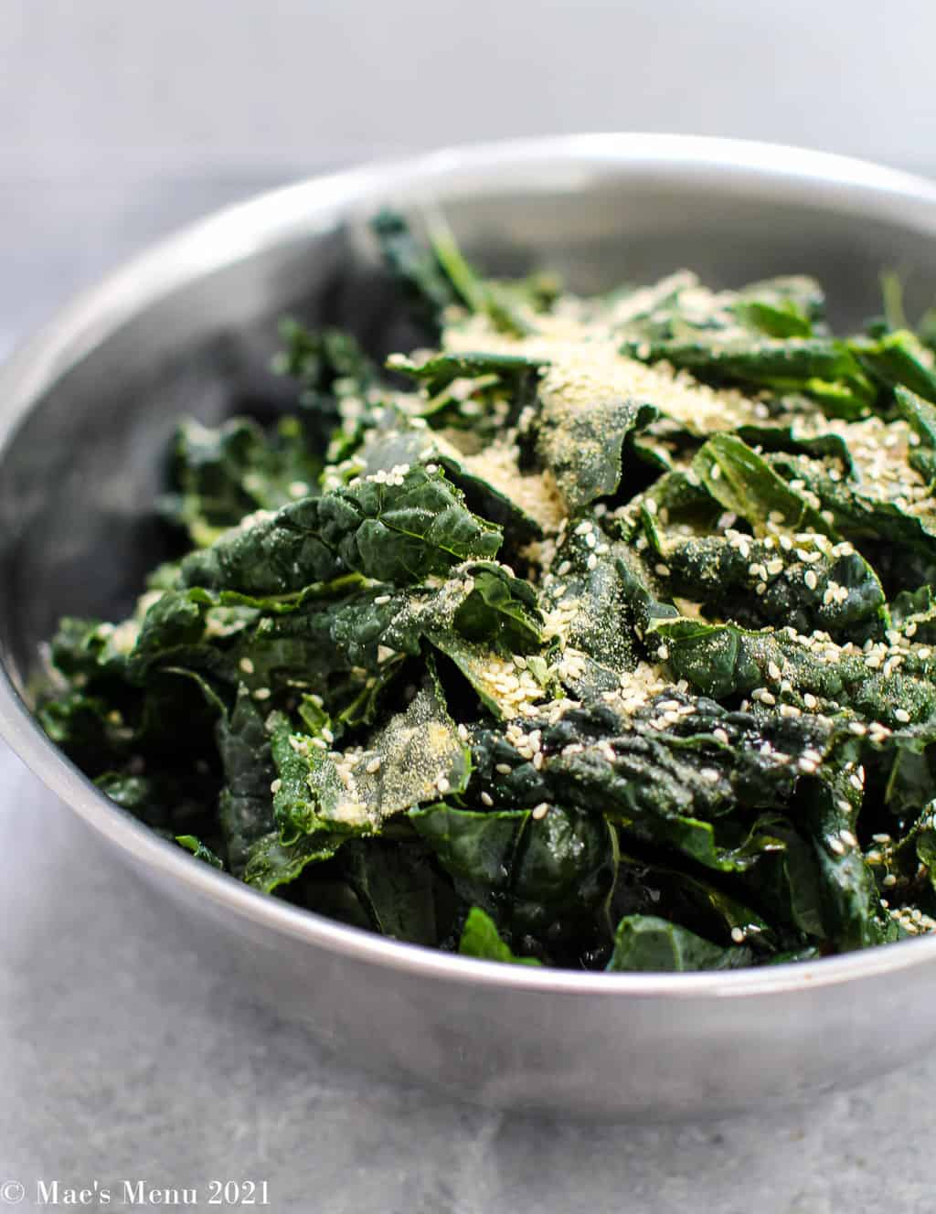 A side shot of kale leaves in a mixing bowl before frying