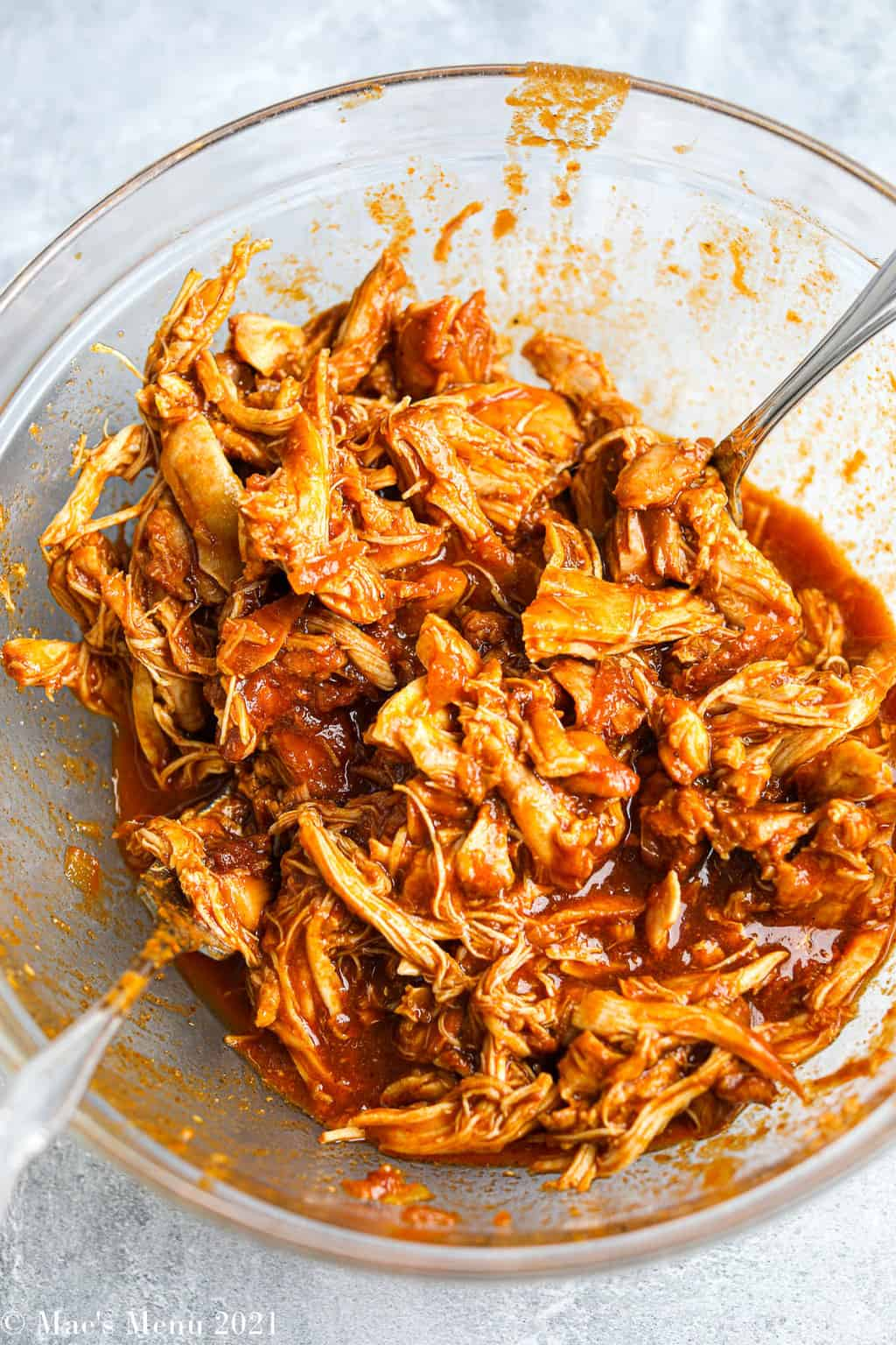 An up-close overheat shot of a glass bowl of shredded barbecue chicken