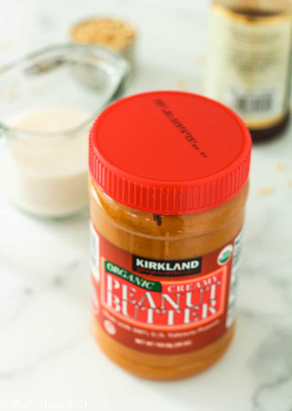 A jar of peanut butter, almond milk, vanilla extract, and peanut butter on a countertop