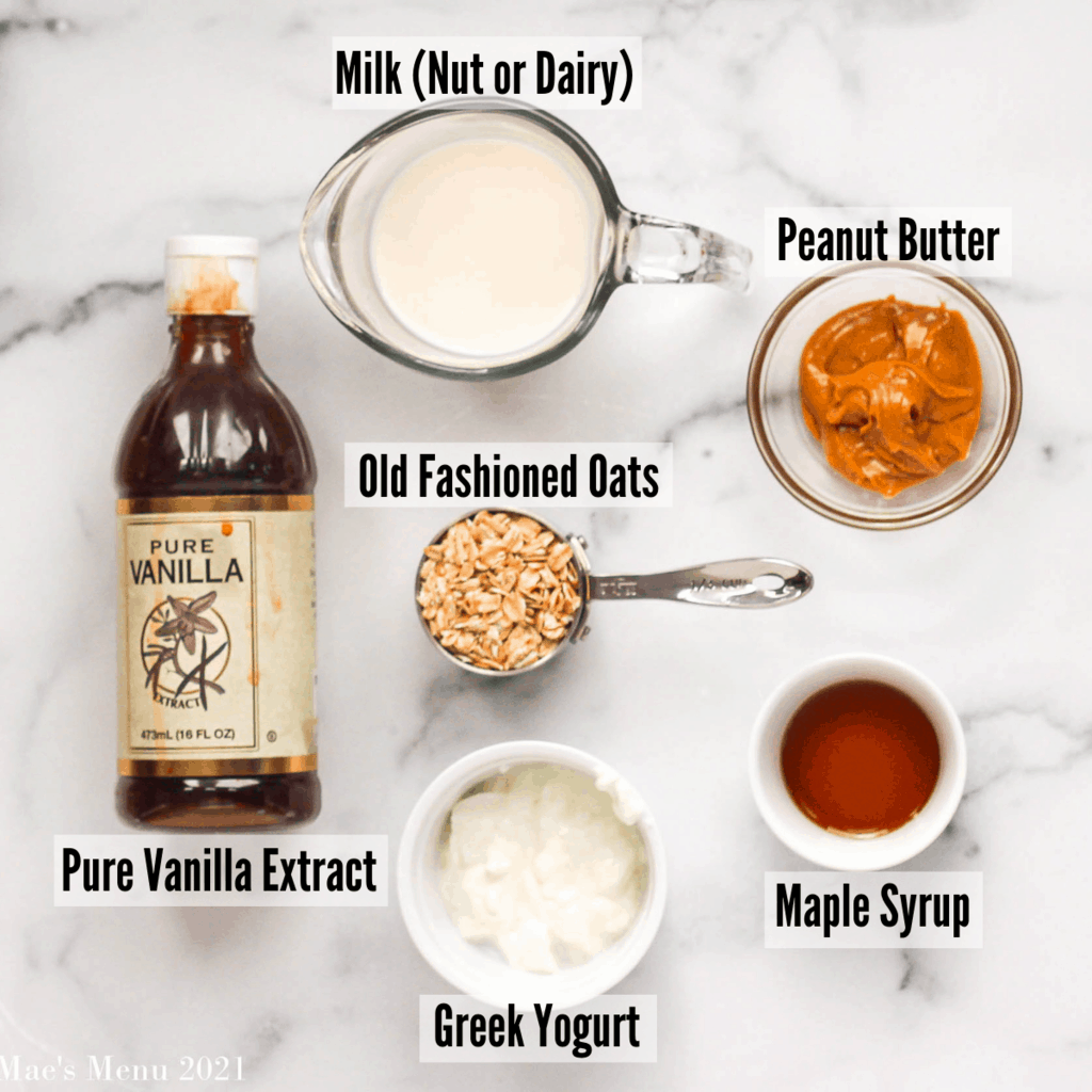 All the ingredients for peanut butter overnight oats: milk, pure vanilla extract, peanut butter, old fashioned oats, maple syrup, and greek yogurt