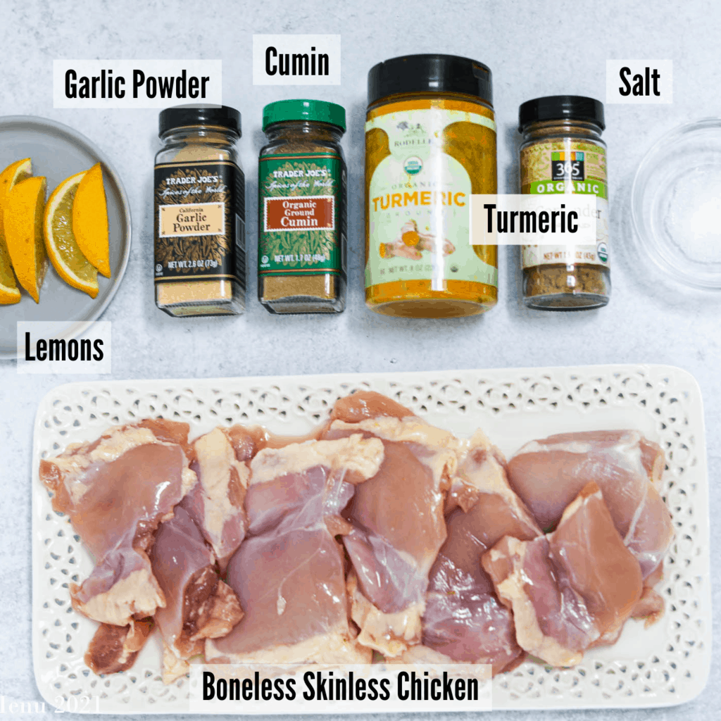 All the ingredients for this recipe: lemons, garlic powder, cumin, turmeric, salt, and boneless skinless chicken.