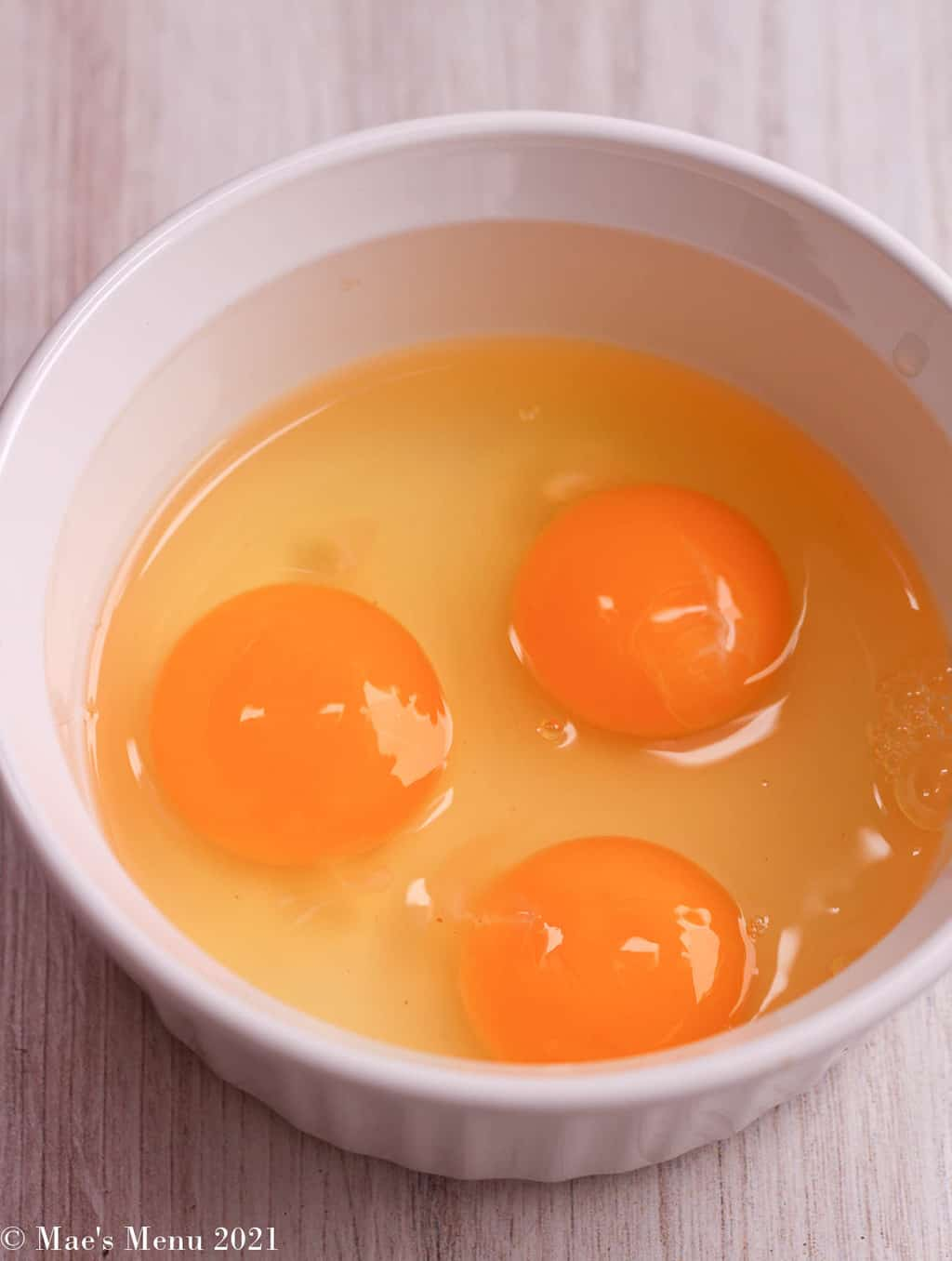 Three large cracked eggs in a white bowl