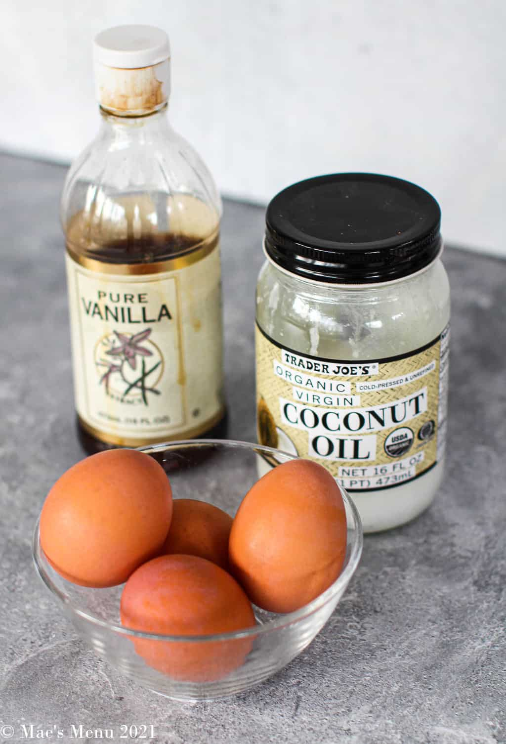 Sweet potato ingredients on the counter: a dish of eggs, a jar of coconut oil and vanilla extract
