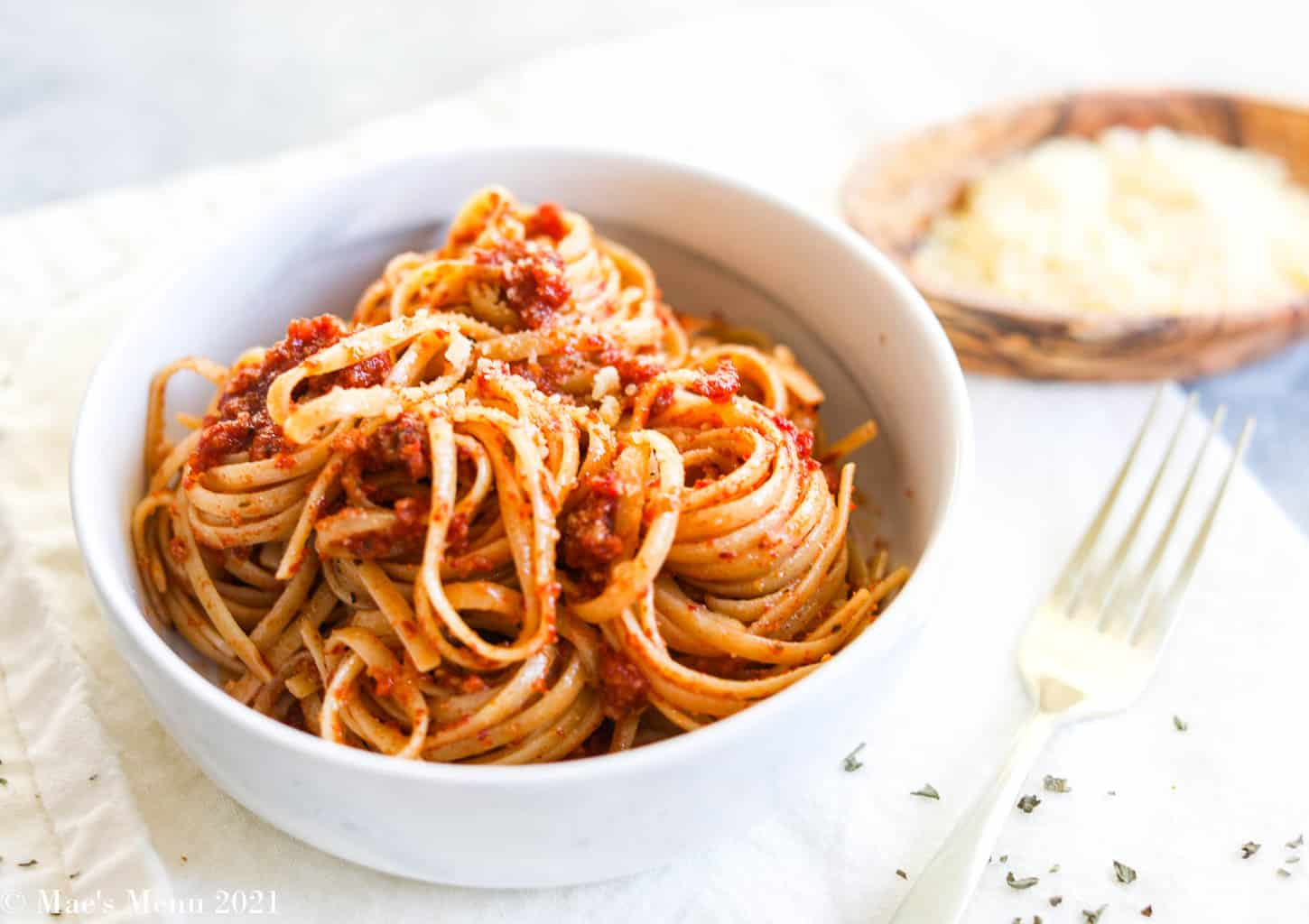A side angle shot of a dish of pasta tossed with tomato (red) pesto