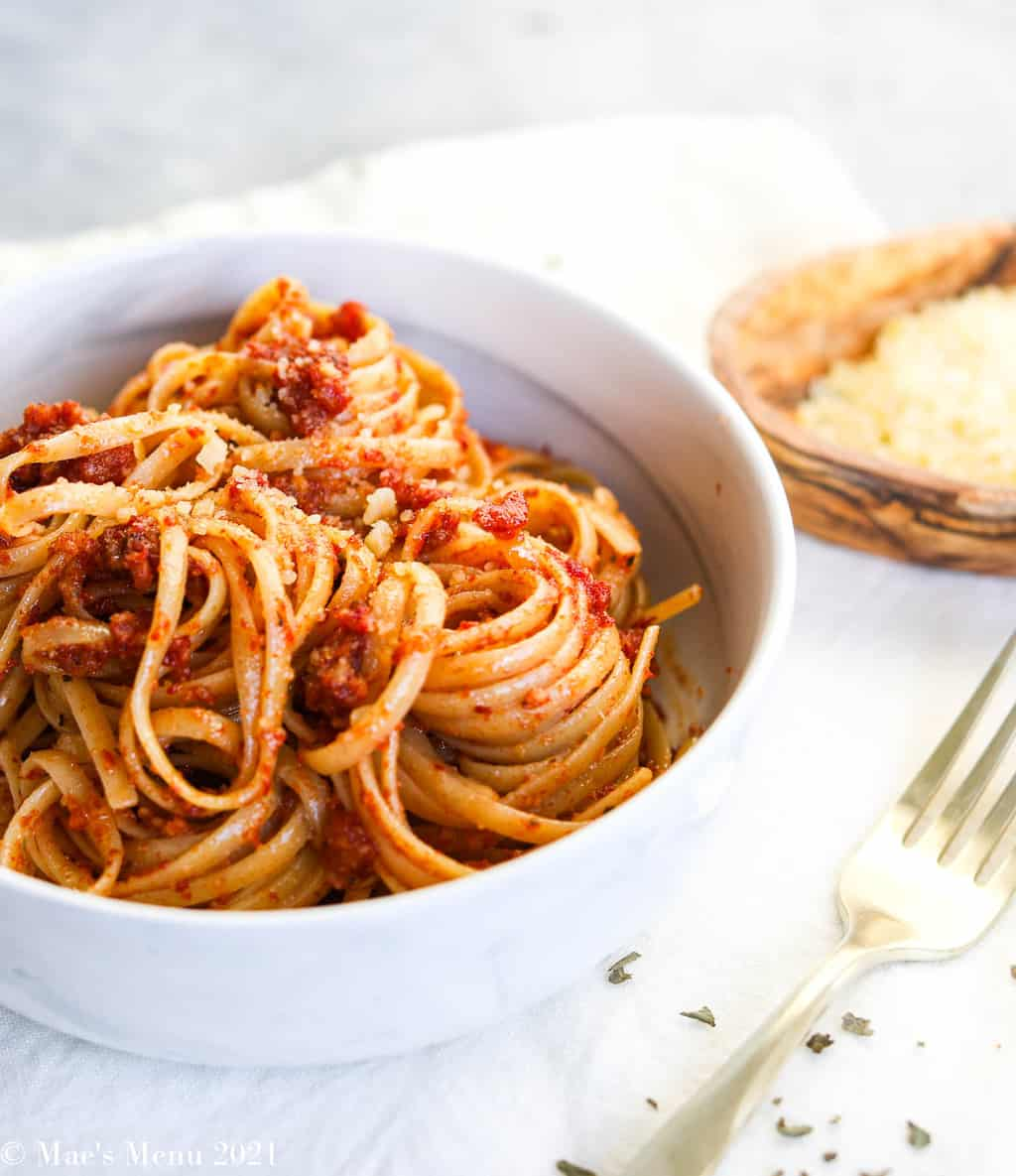 A side angled shot of linguine tossed with tomato red pesto in a white bowl