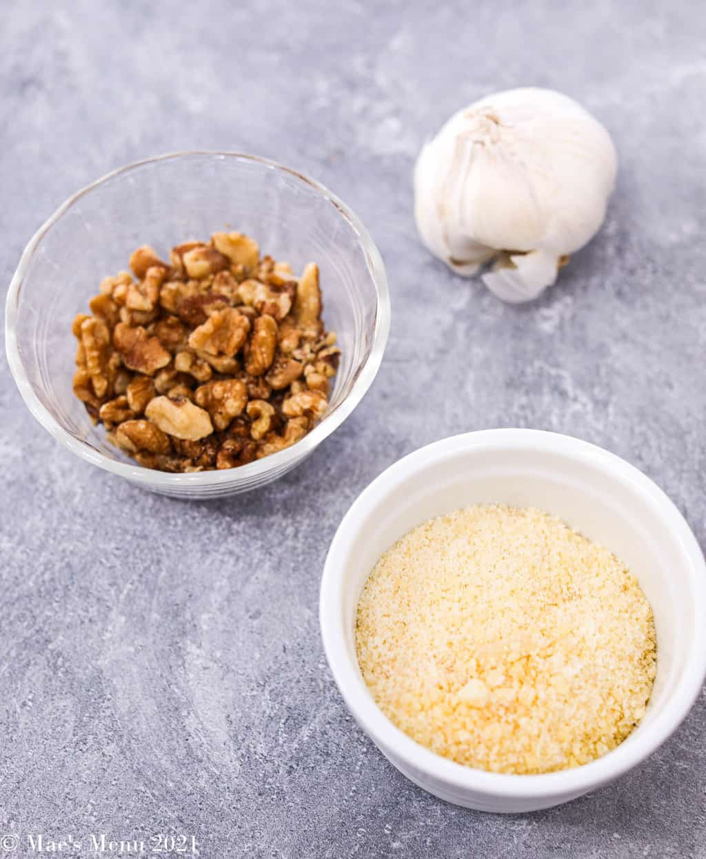 a clove of garlic, a dish of walnuts, and a small dish of grated parmesan cheese
