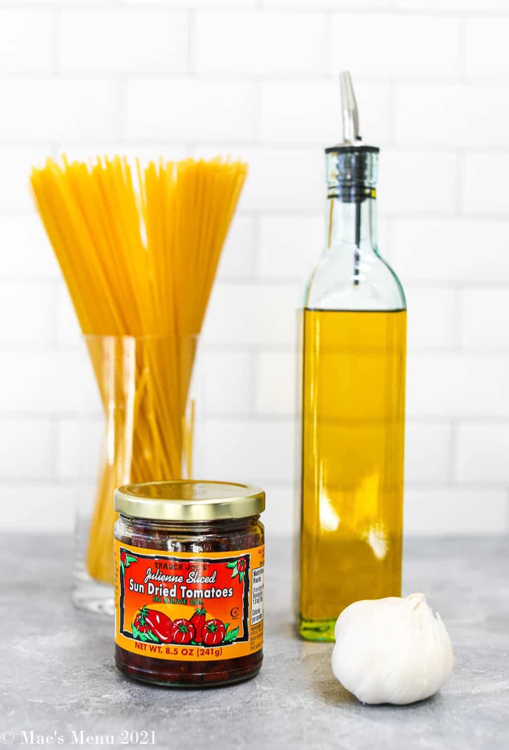 Some ingredients for tomato pesto: garlic, olive oil, sundried tomatoes packed in oil, and a cup of dried linguine