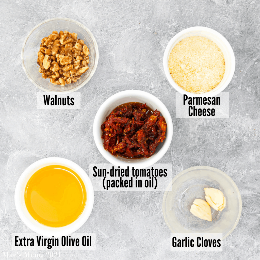All the ingredients for tomato (or red) pesto: walnuts, parmesan cheese, sun-dried tomatoes, garlic cloves, extra virgin olive oil