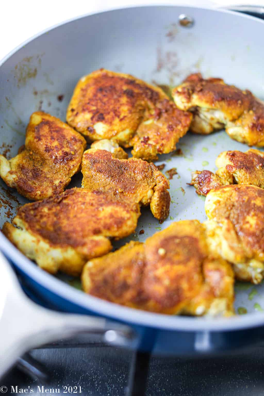Turmeric rubbed chicken cooking in a non-stick pan