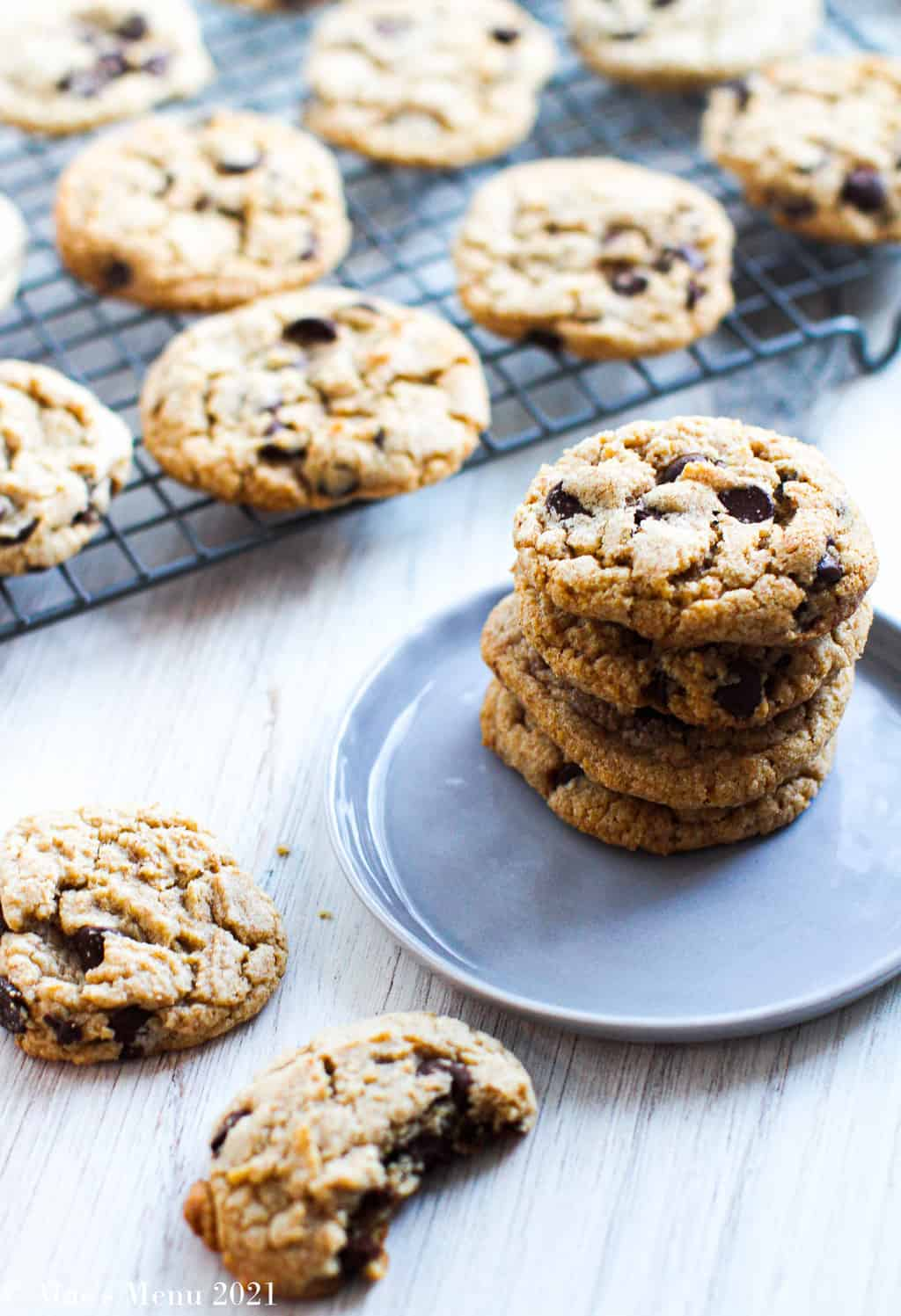 A stack of whole wheat chocolate chip cookies on a blue-gray plate next to cookies on the counter and a cooling rack full of them behind the plate