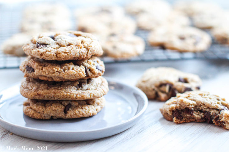 A stack of whole wheat chocolate chips cookies on a plate next to cookies on the counter and on a cooling rack