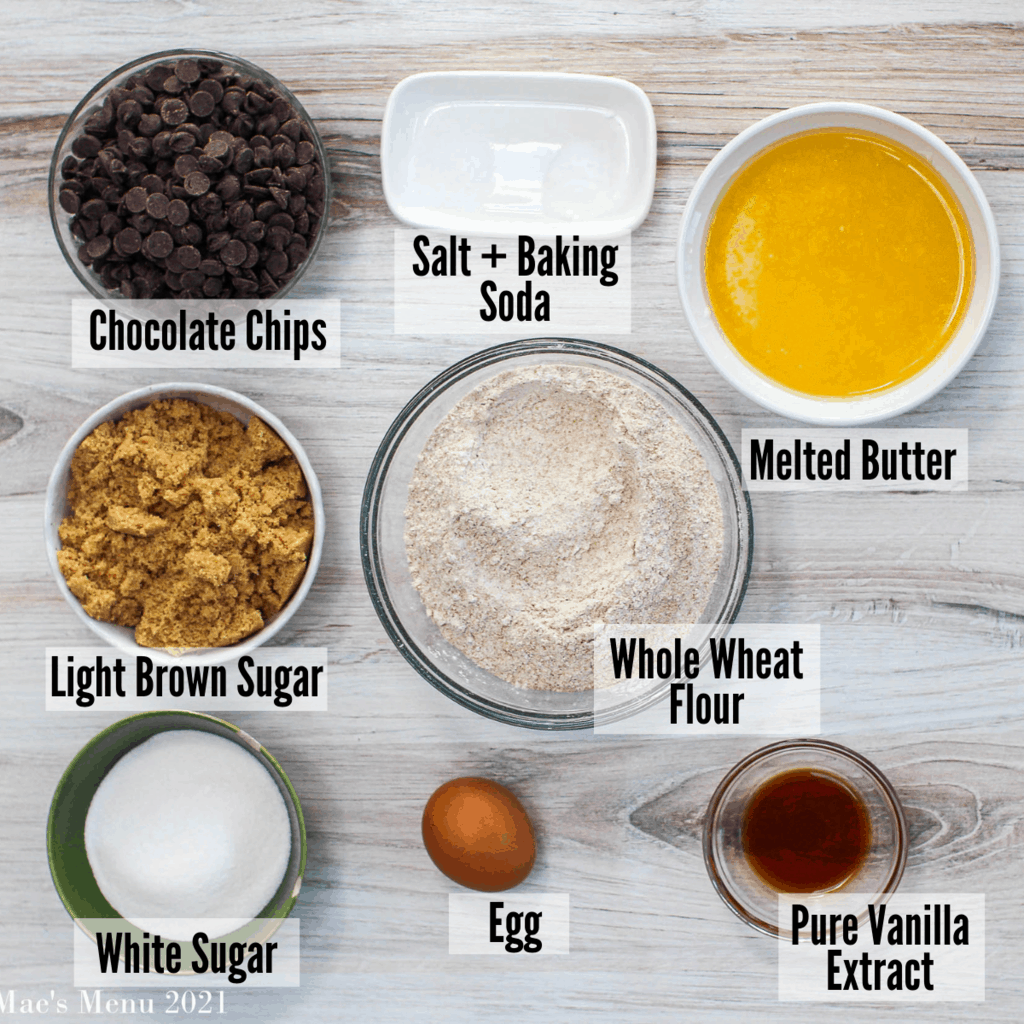 Ingredients for whole wheat chocolate chip cookies: whole wheat flour, chocolate chips, salt & baking soda, melted butter, pure vanilla extract, egg, white sugar, and light brown sugar