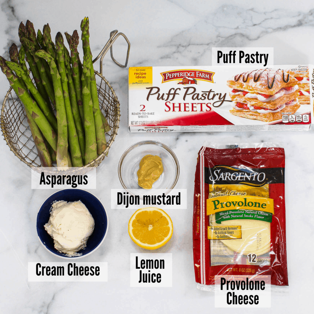 All of the ingredients for the cheesy asparagus tarts: asparagus, puff pastry, dijon mustard, provolone cheese, lemon juice, and cream cheese