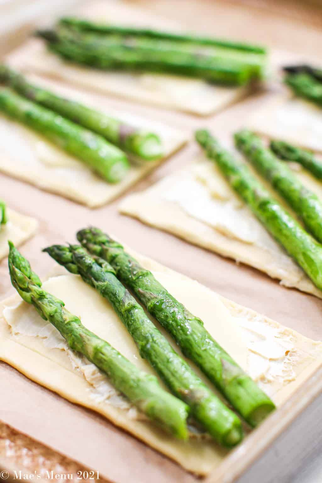 The asparagus tarts on a parchment paper-lined baking sheet, ready to go into the oven