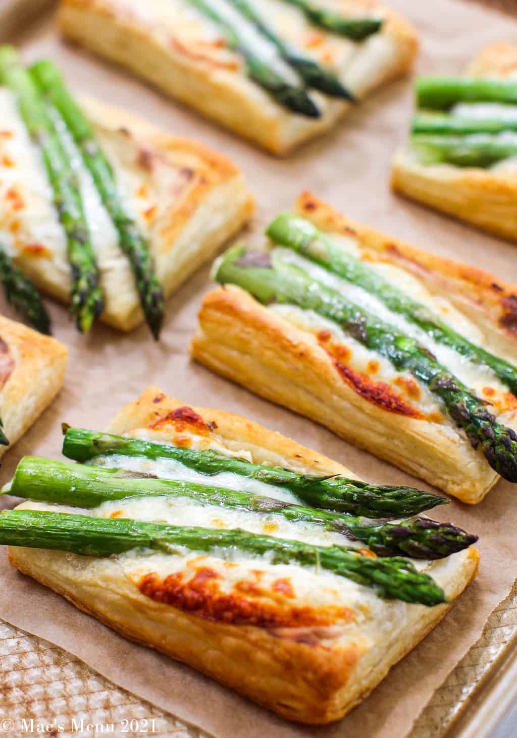 An up-close side shot of fresh baked cheesy asparagus tarts