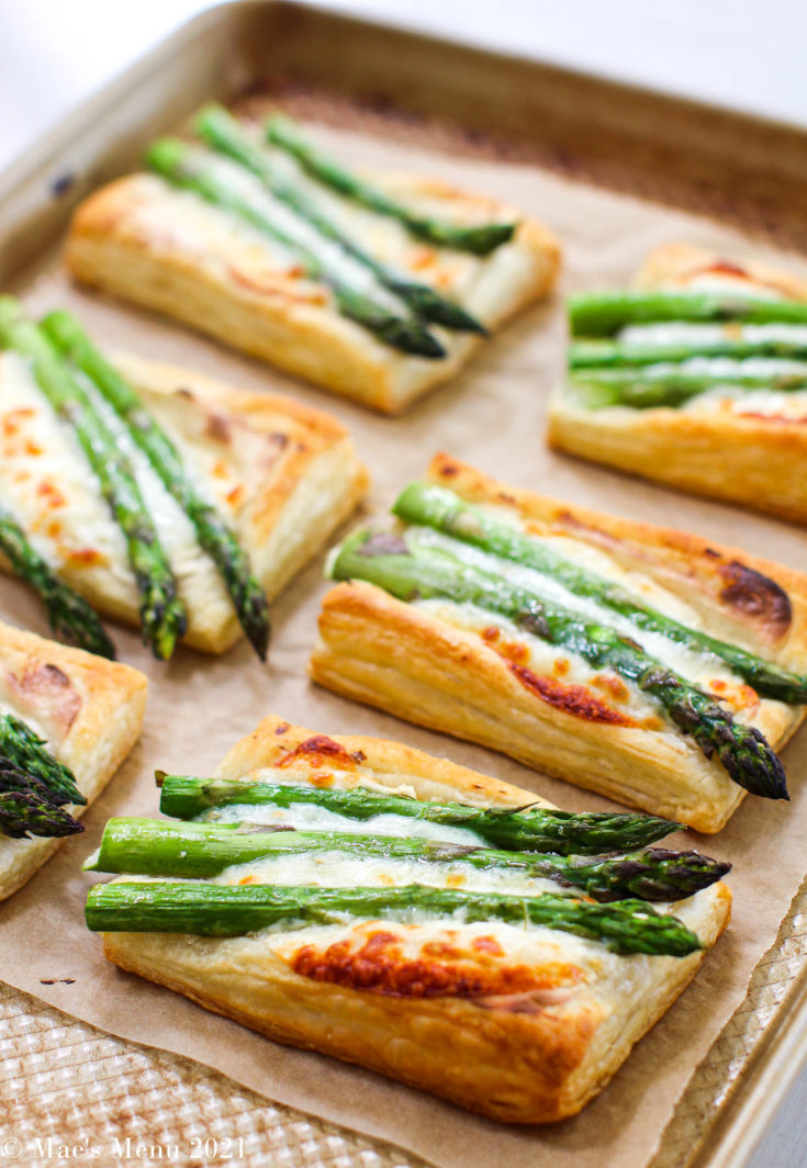 An elevated angle shot of a tray of cheesy asparagus tarts