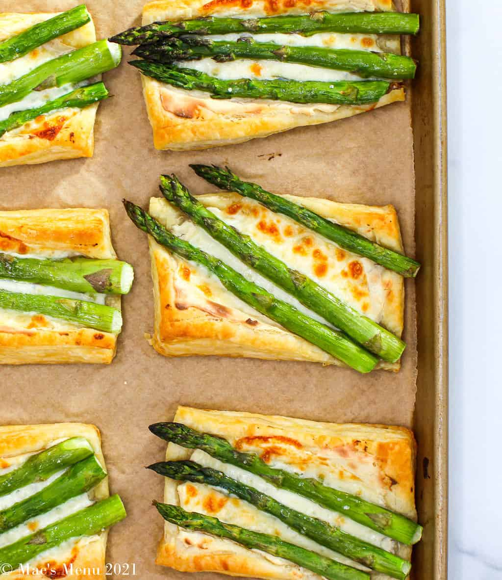 An overhead shot of cheesy asparagus tarts on a baking sheet