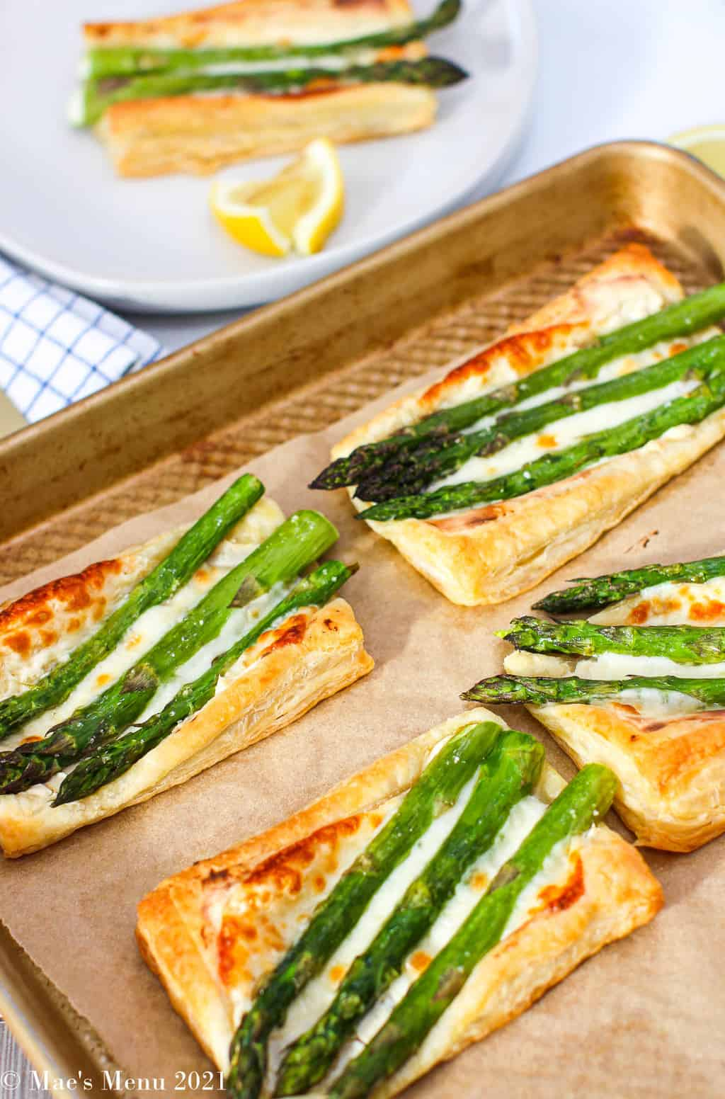 A baking sheet of easy and cheesy asparagus tarts with a white plate with a tart on it in the background