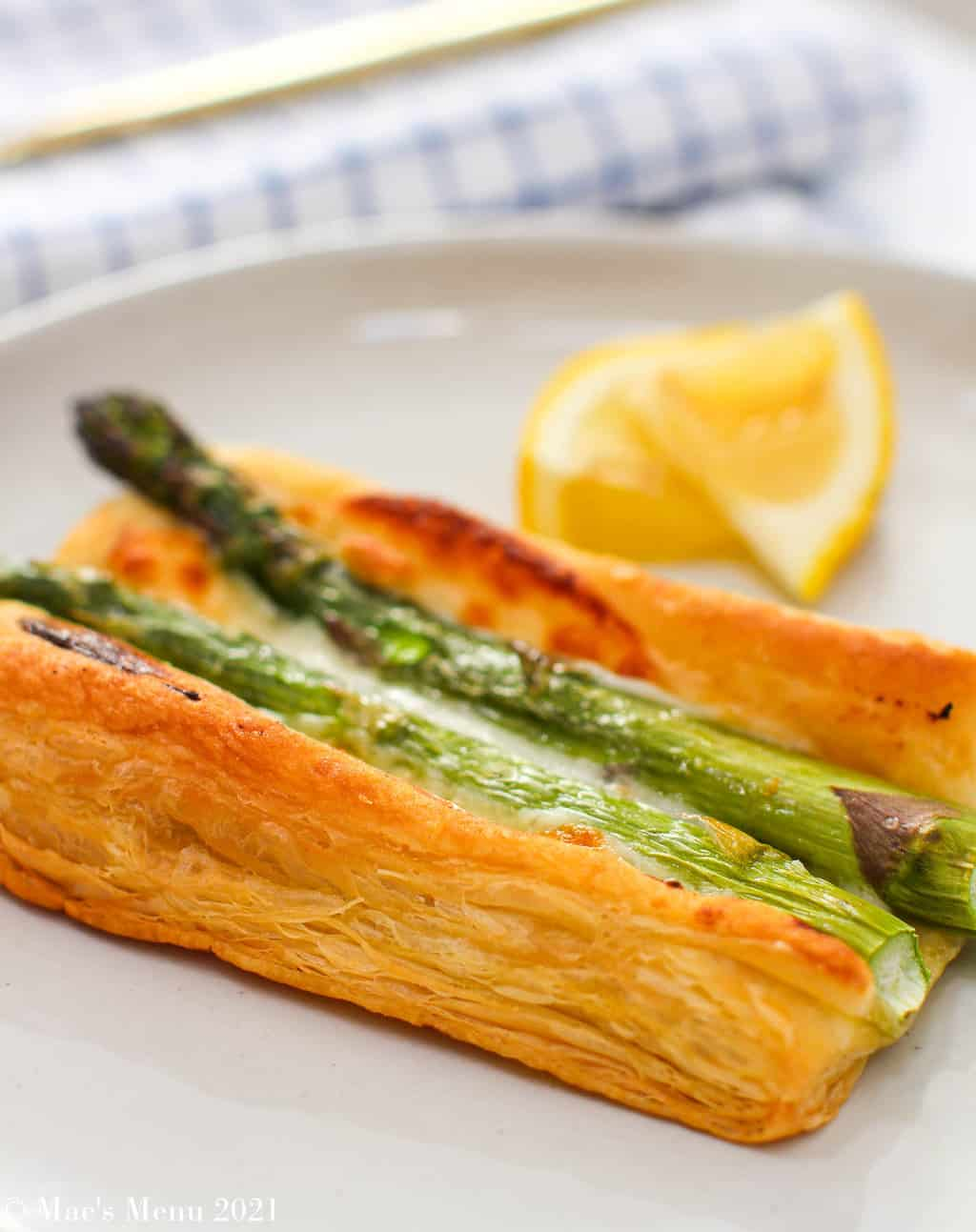 An up-close side shot of an easy and cheesy asparagus tart on a white plate