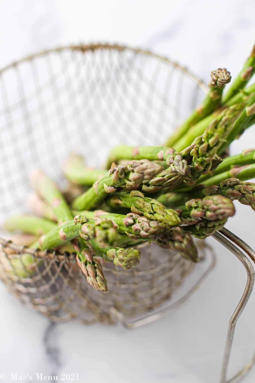 Angled overhead shot of a strainer full of asparagus spears