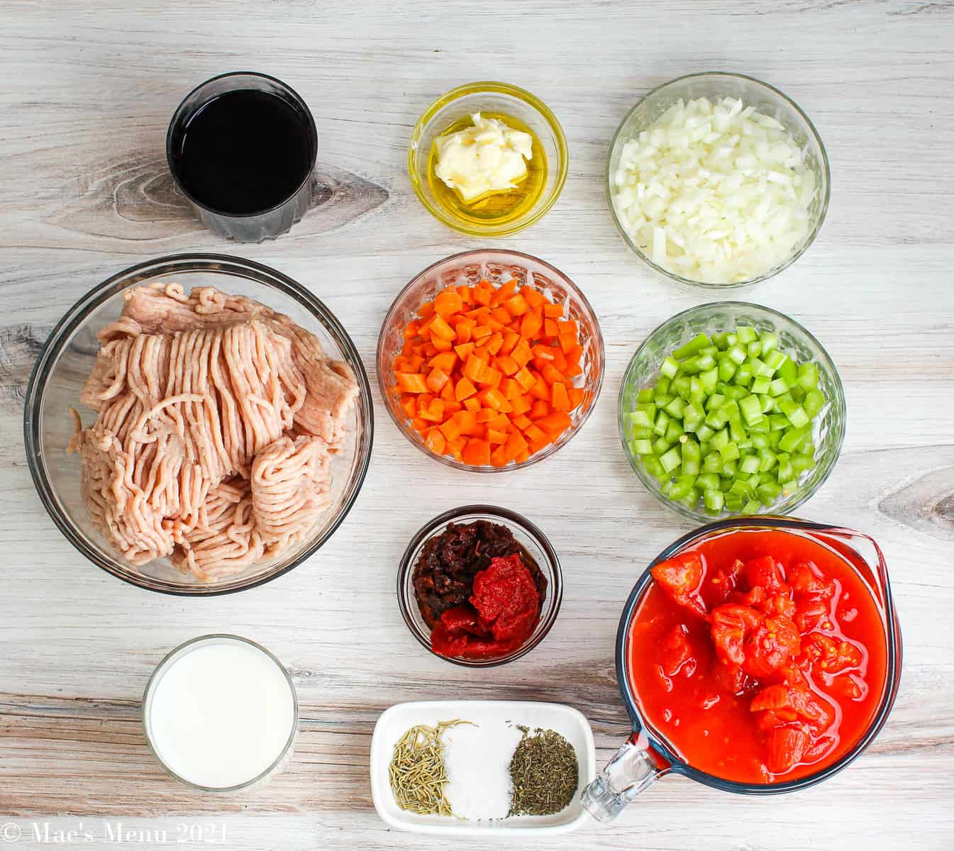 An overhead shot of all the ingredients for chicken bolognese: red wine, butter & olive oil, onions, celery, carrots, canned tomatoes, tomato paste and sundried tomatoes, and more