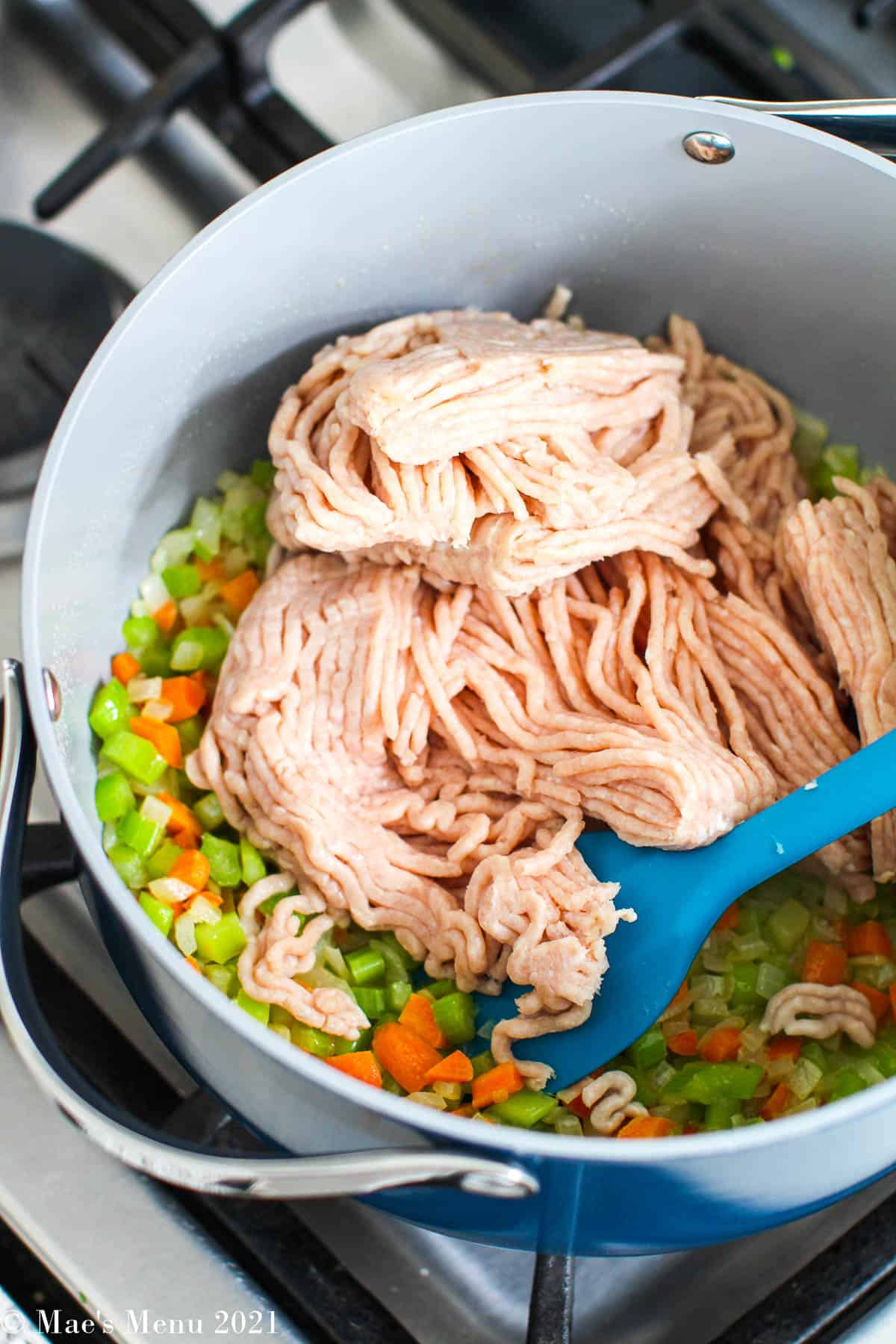 Adding chicken to the stockpot with the veggies